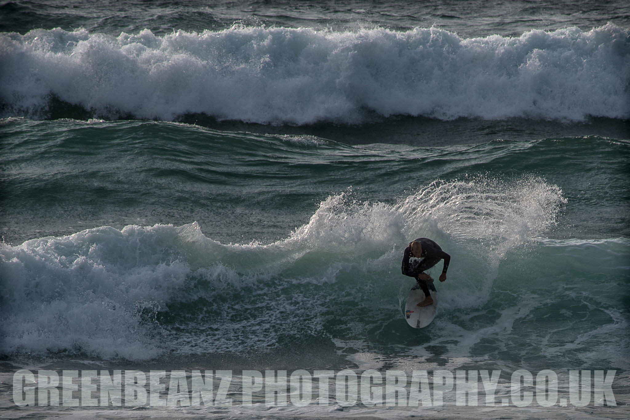 Surfer crouching on board riding a wave off the Cornish coast