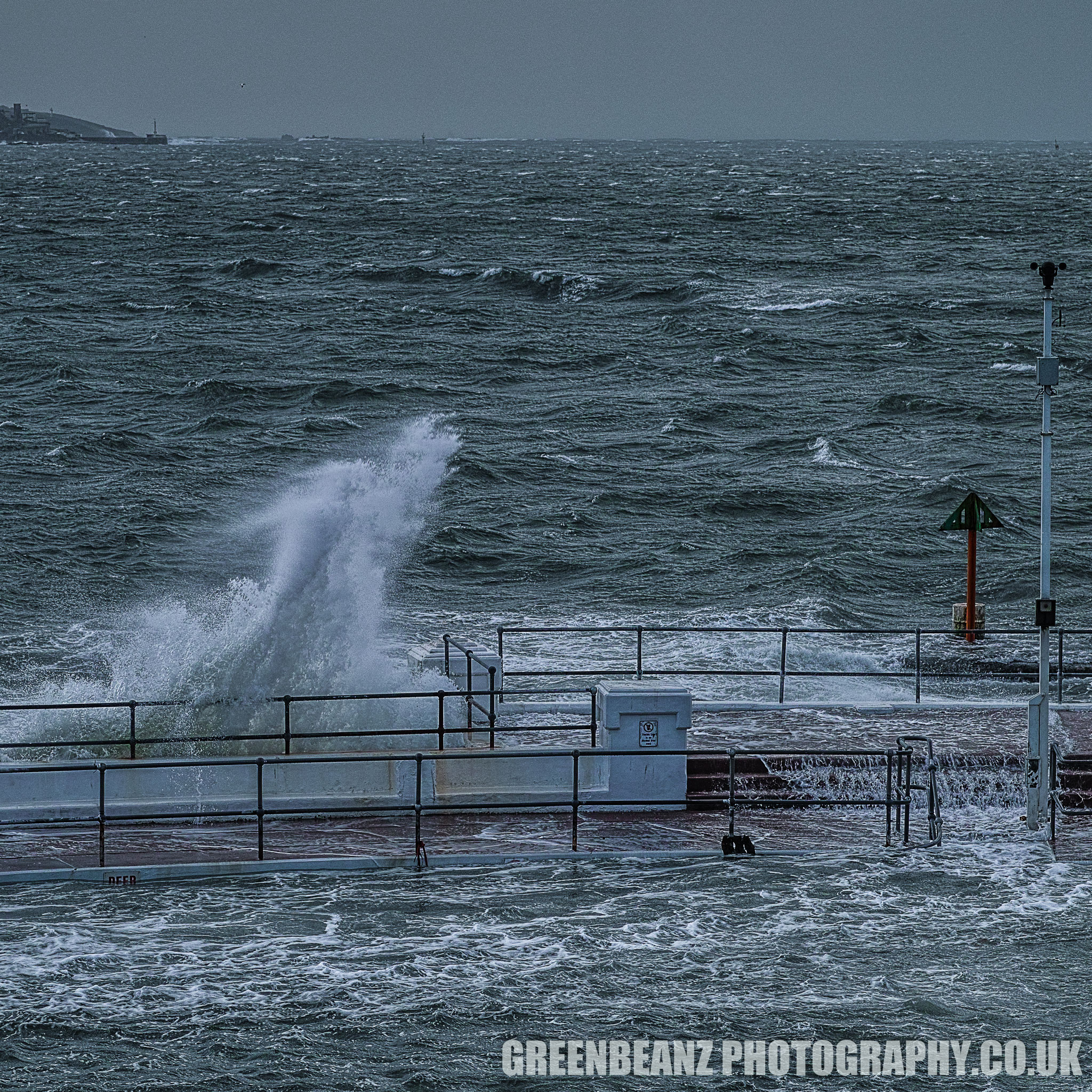 Storm Waves Plymouth Hoe. The Lido pool is buffeted and flooded by the sea