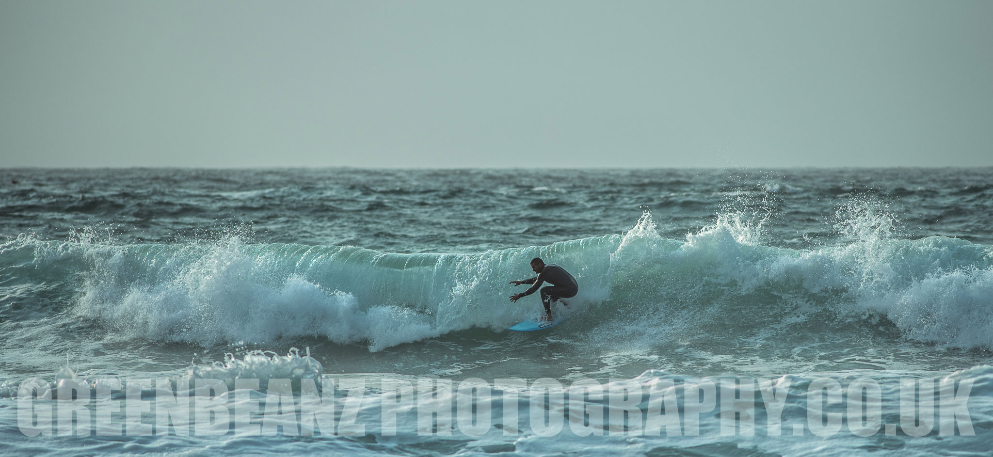 Surfer rides a wave of a messy sea in September at Newquay