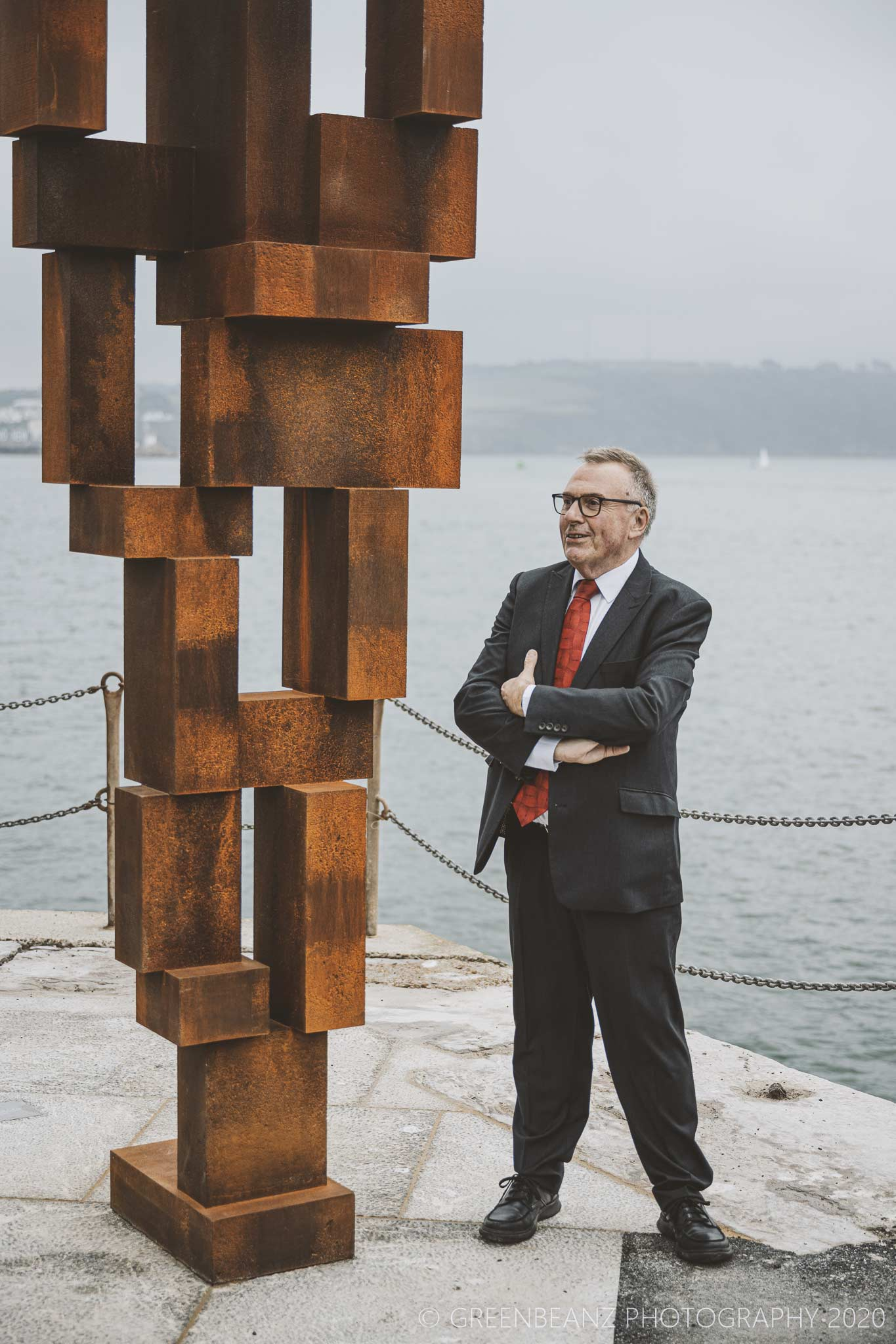 Tudor Evans stands next to Antony Gormleys sculpture in Plymouth