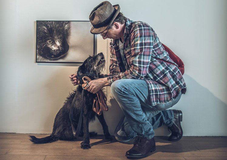 Artist Kevin Attwod with Dog Josh below photograph of dogs nose in a gallery